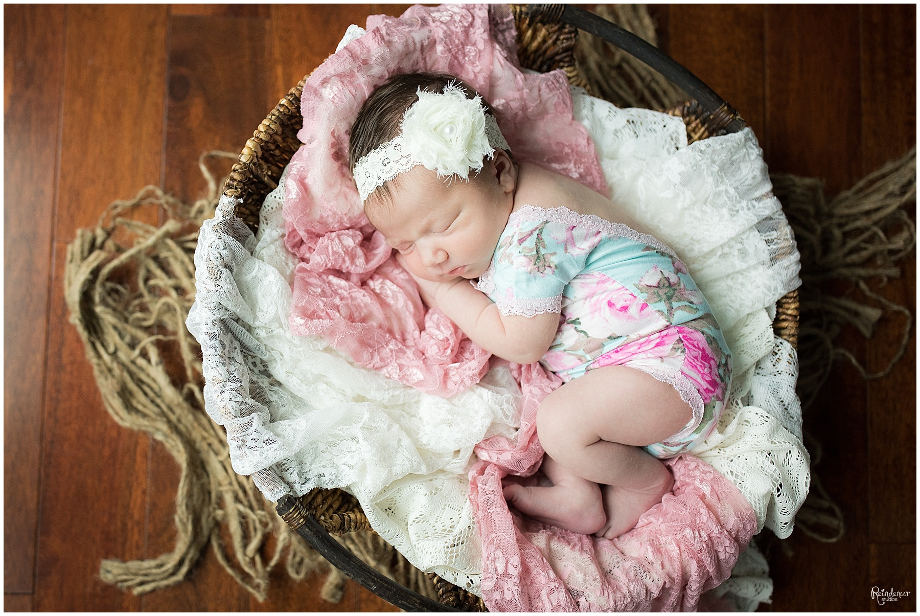 This newborn girl is in a basket with lace and a pretty bow during her newborn session in Indiana.