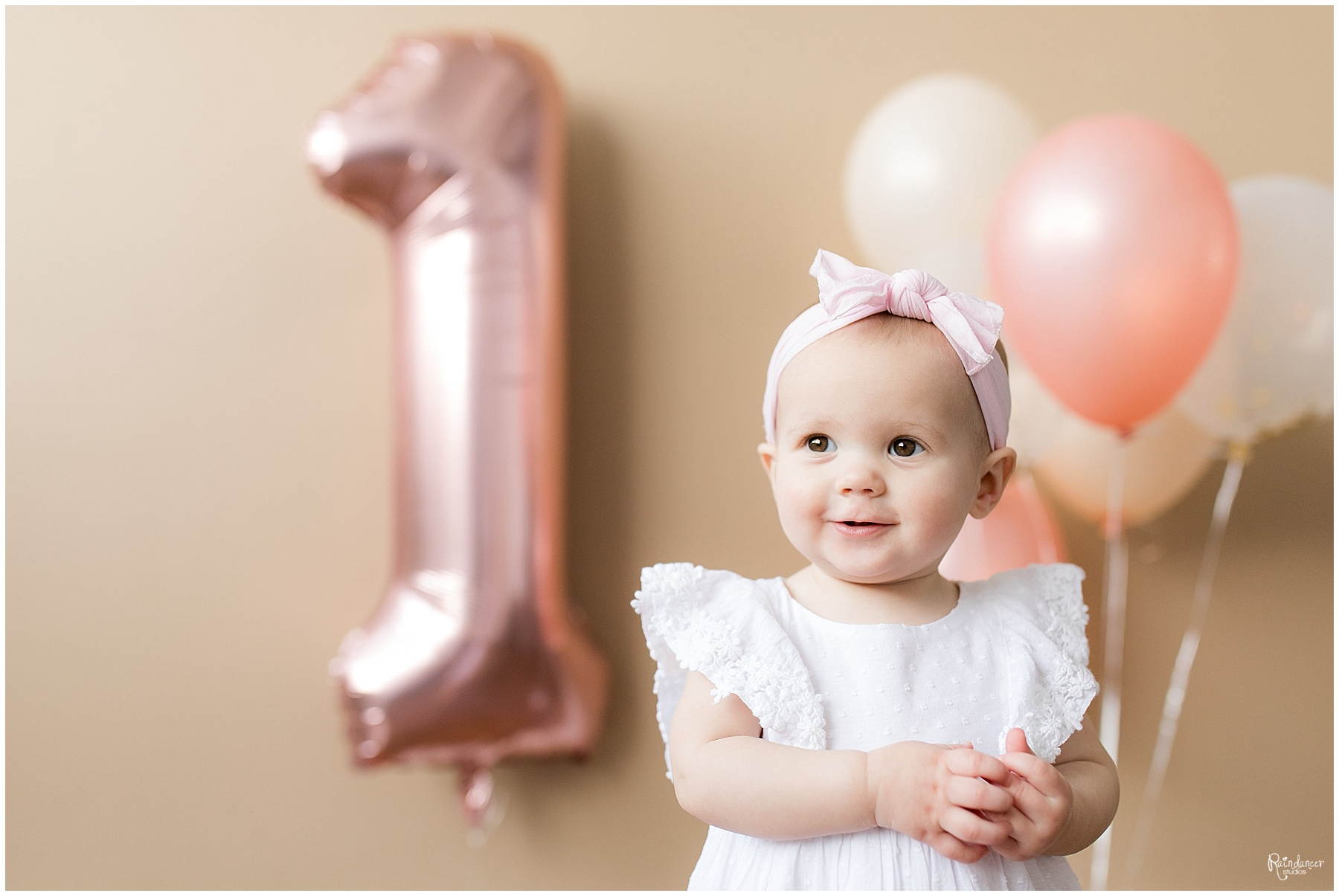 One year old baby girl in pink bow with balloons by Raindancer Studios Indianapolis Children Photographer Jill Howell