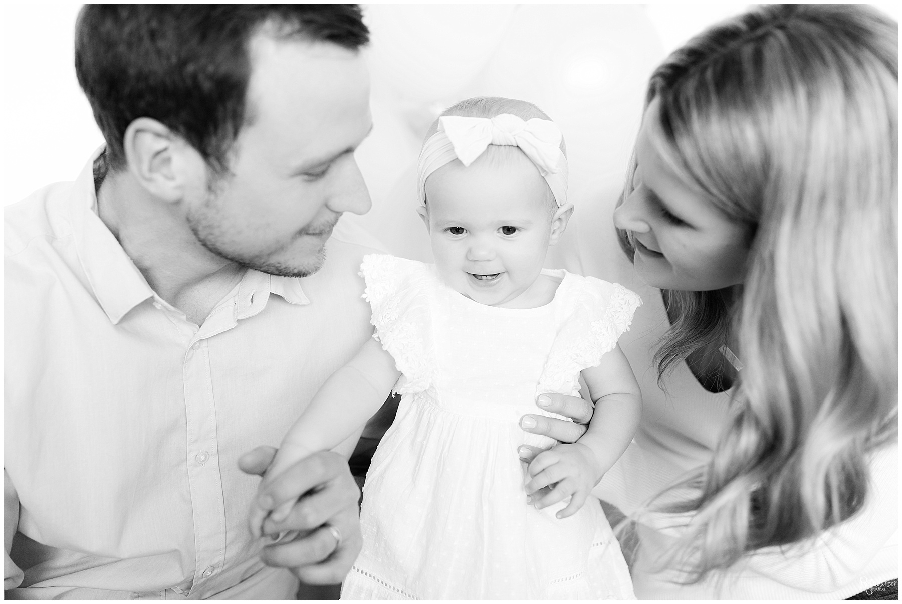 Parents looking at one year old baby girl by Raindancer studios Indianapolis Children Photographer Jill Howell
