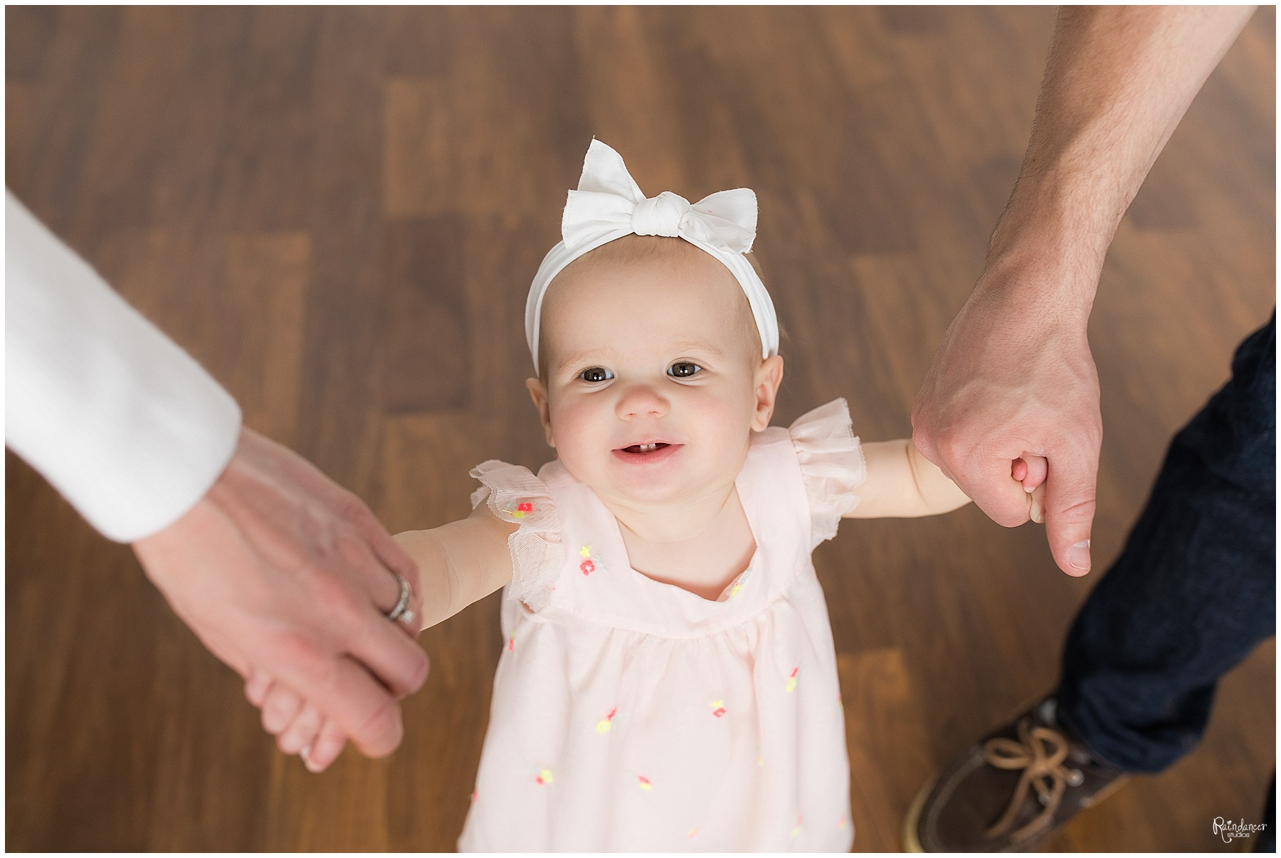 Parents holding hands with one year old baby girl by Raindancer Studios Indianapolis Children Photographer Jill Howell