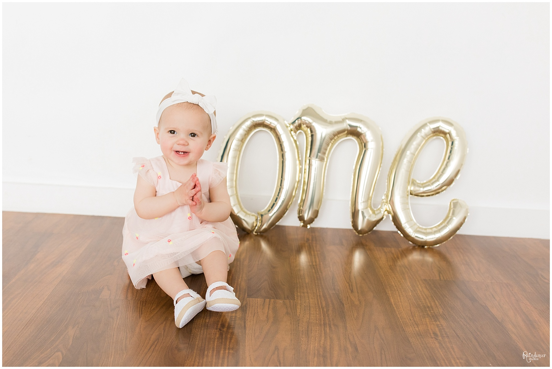 One year old baby girl smiling in a pink bow by Raindancer Studios Indianapolis Children Photographer Jill Howell