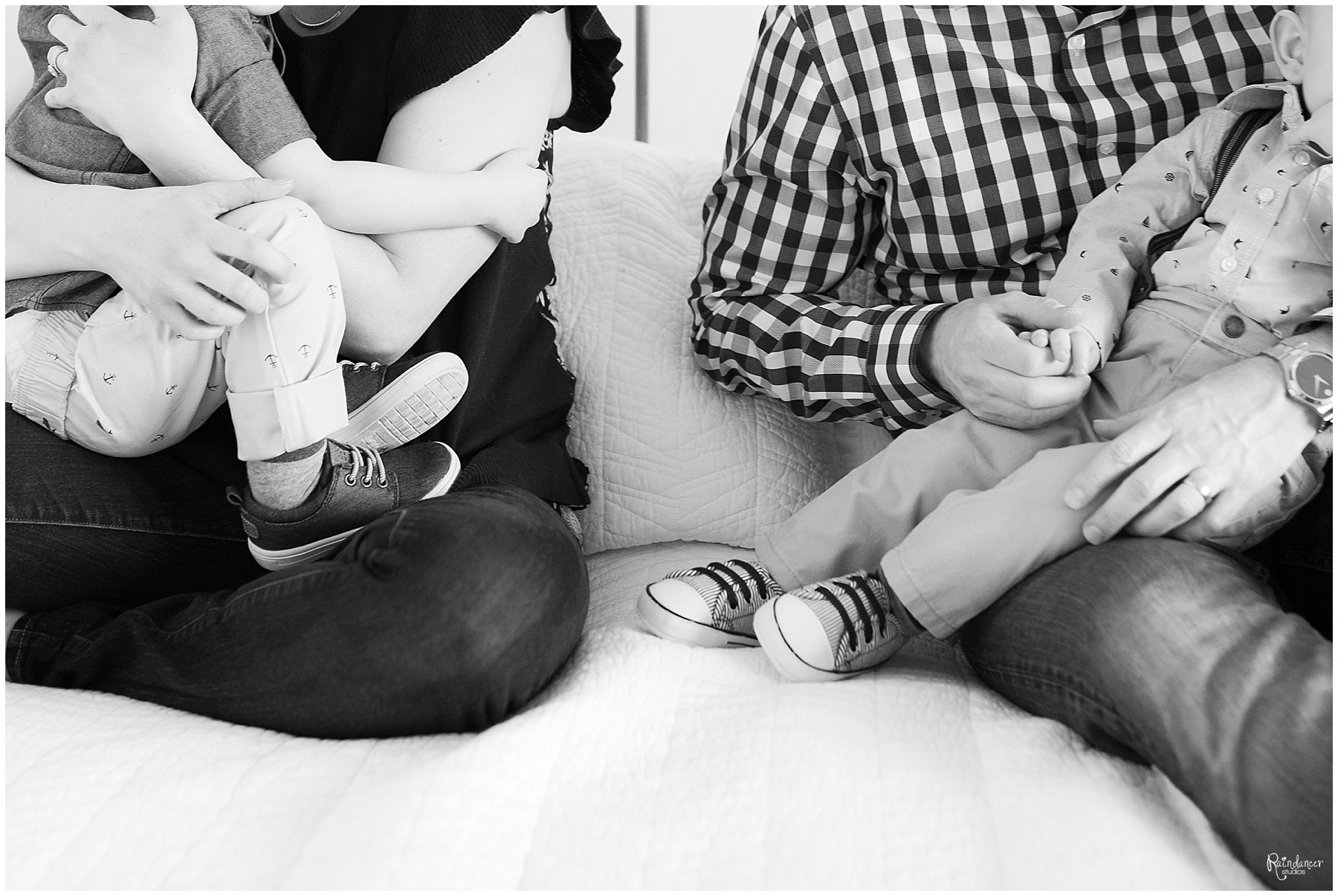 Bothers sitting on their parents laps on couch by Raindancer Studios Indianapolis Family Photographer Jill Howelll