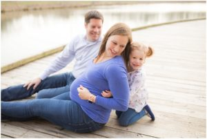 Family of three sitting on the wooden dock with little girl holding mom's pregnant belly.