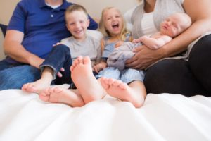 Family of five on bed in Columbus Indiana home during newborn session.