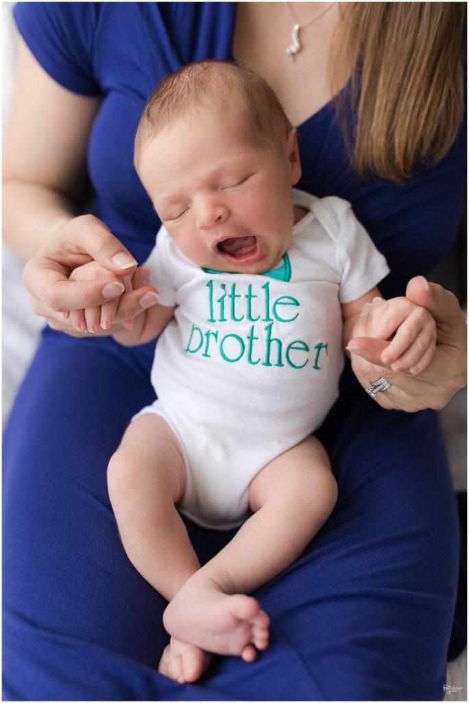 "Mother in blue dress holding newborn baby boy in ""big brother"" onesie by Raindancer Studios Indianapolis Newborn Photographer Jill Howell"