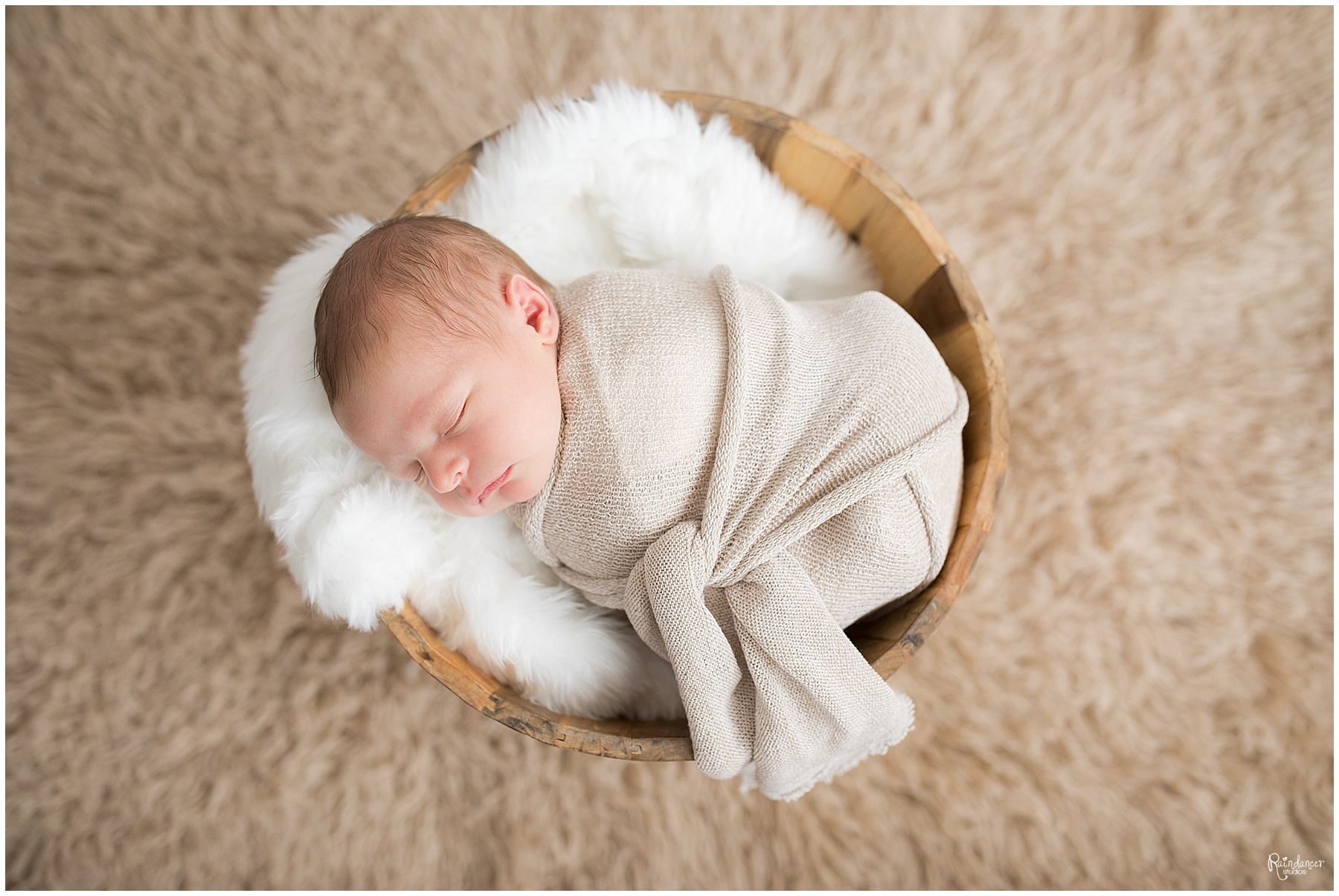 Newborn baby boy sleeping in a swaddle in a rustic bucket by Raindancer Studios Indianapolis Newborn Photographer Jill Howell