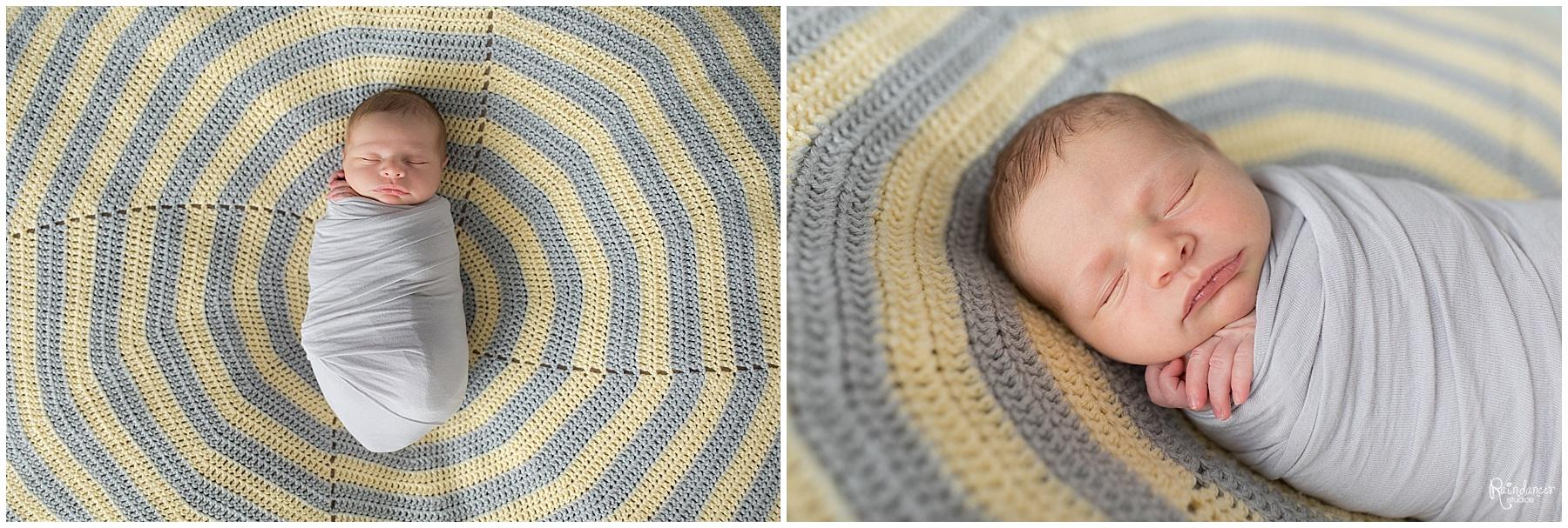 Newborn baby boy sleeping on striped blanket in a swaddle by Raindancer Studios Indianapolis Newborn Photographer Jill Howell