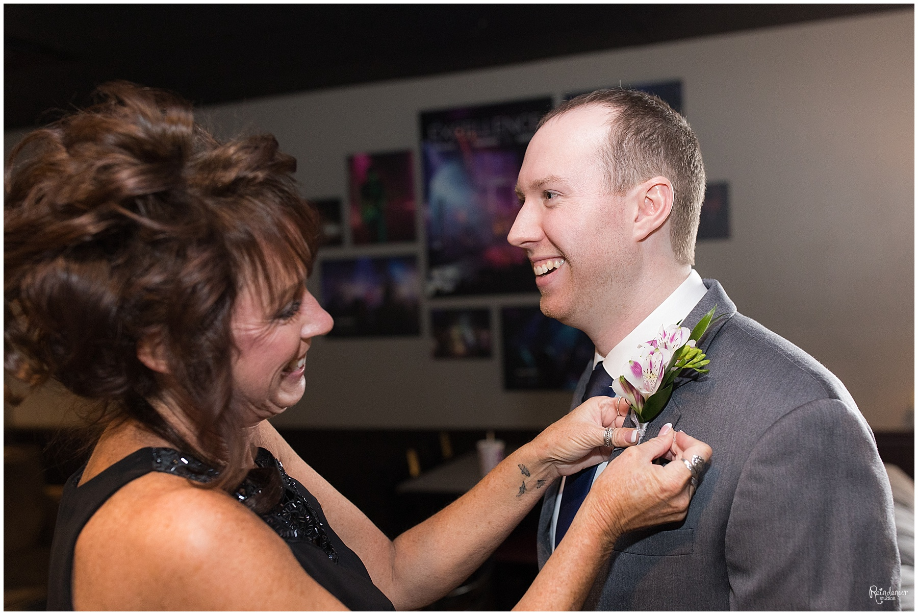 Mother of the groom putting on son's boutonniere by Indianapolis Wedding Photographer Jill Howell