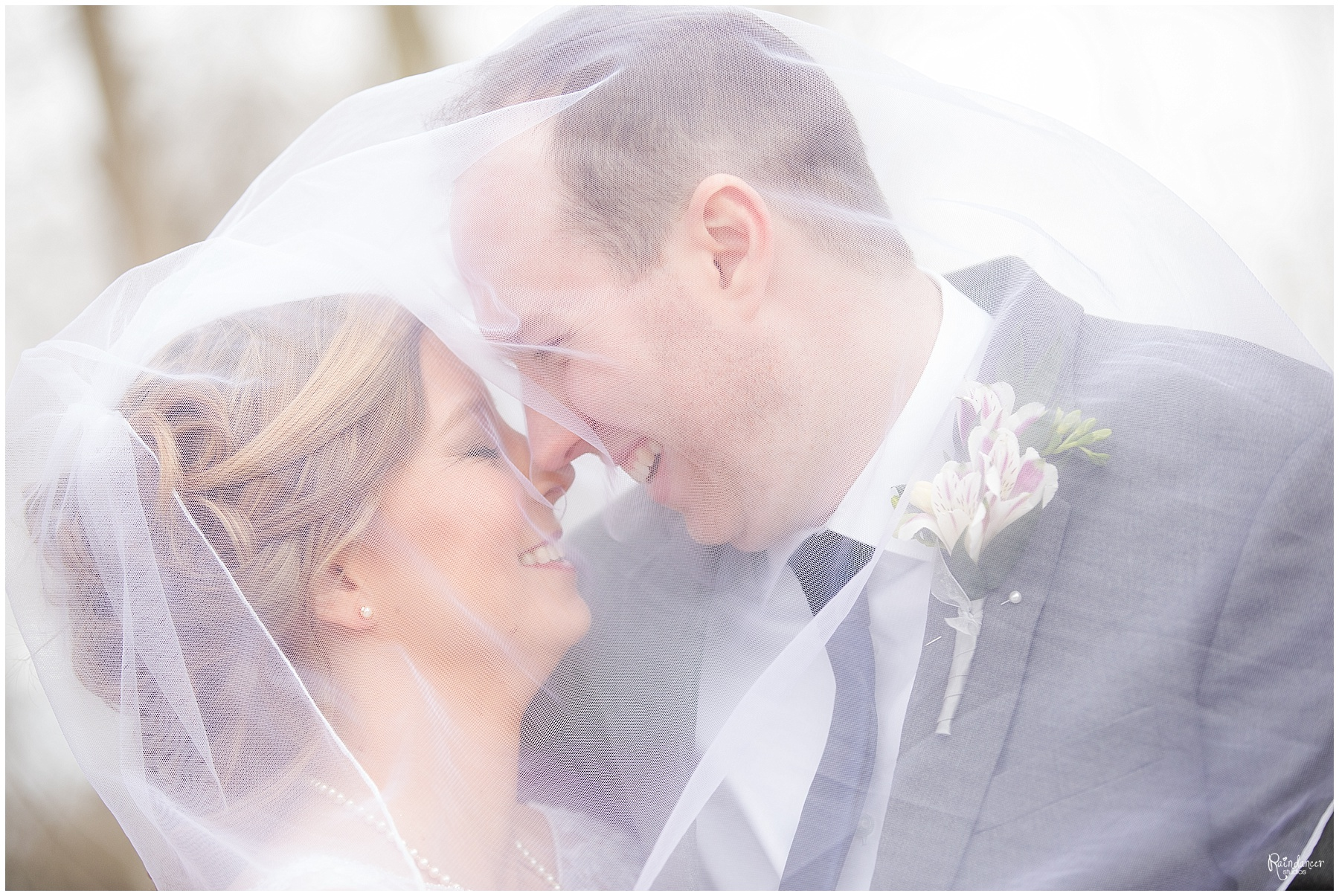 Bride and groom hugging and smiling under veil by Raindancer Studios Indianapolis Wedding photographer Jill Howell
