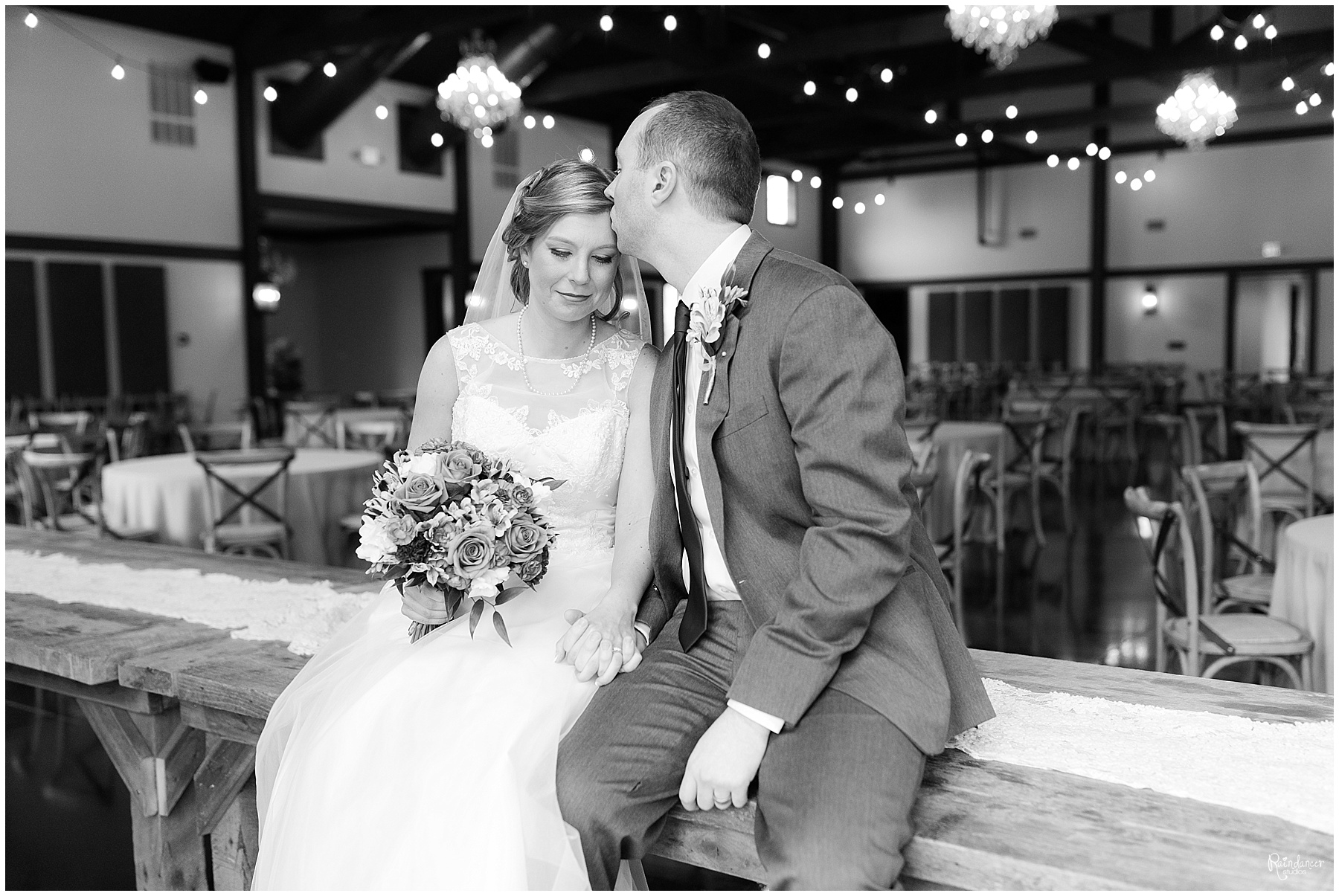 Groom kissing brides forehead while sitting on table by Raindancer Studios Indianapolis Wedding photographer Jill Howell