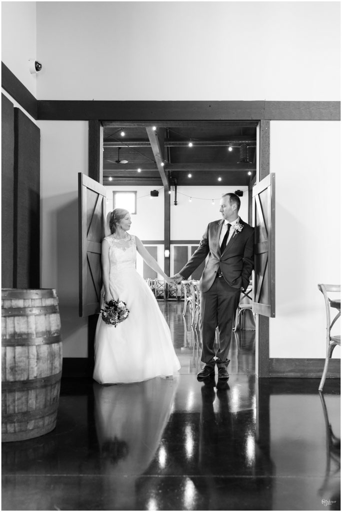 Bride and groom holding hands in a doorway by Raindancer Studios Indianapolis Wedding Photographer Jill Howell