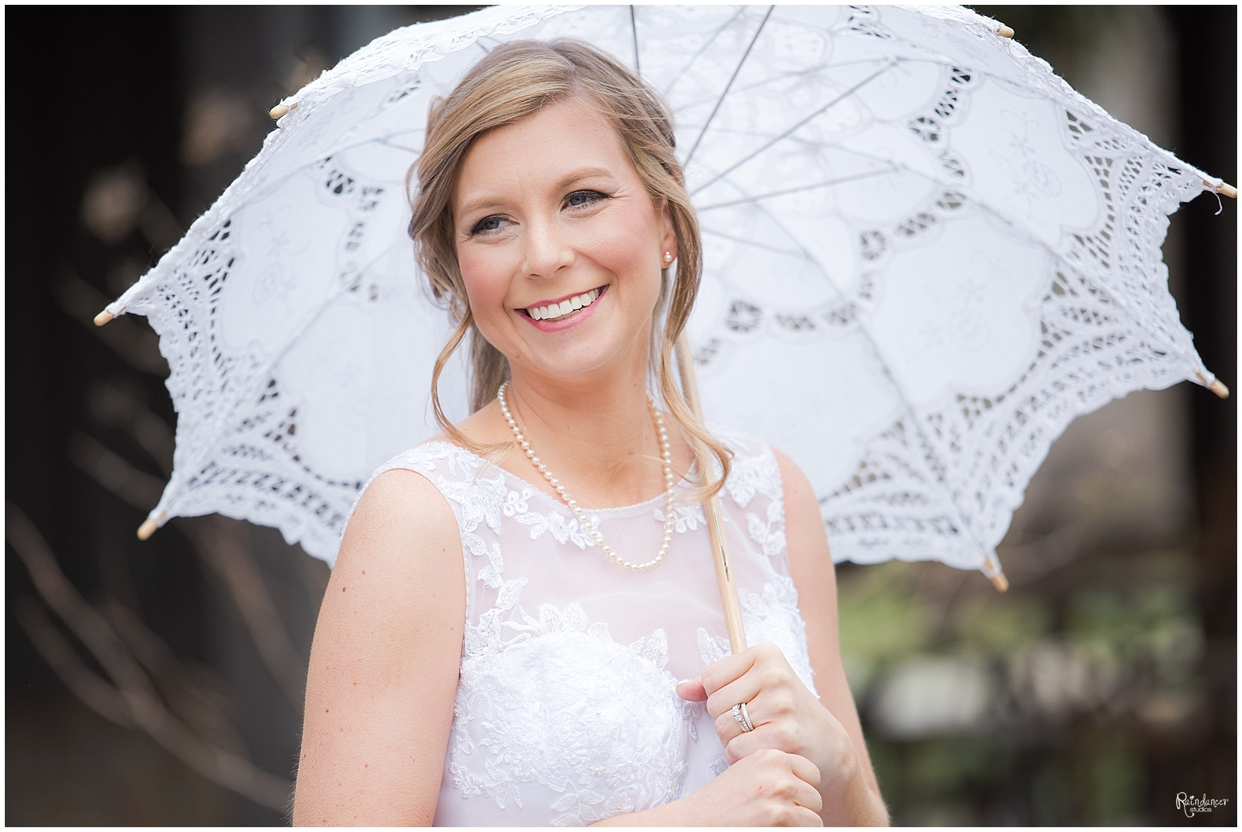 Bride outside holding a white parasol umbrella by Raindancer Studios Indianapolis Wedding Photographer Jill Howell