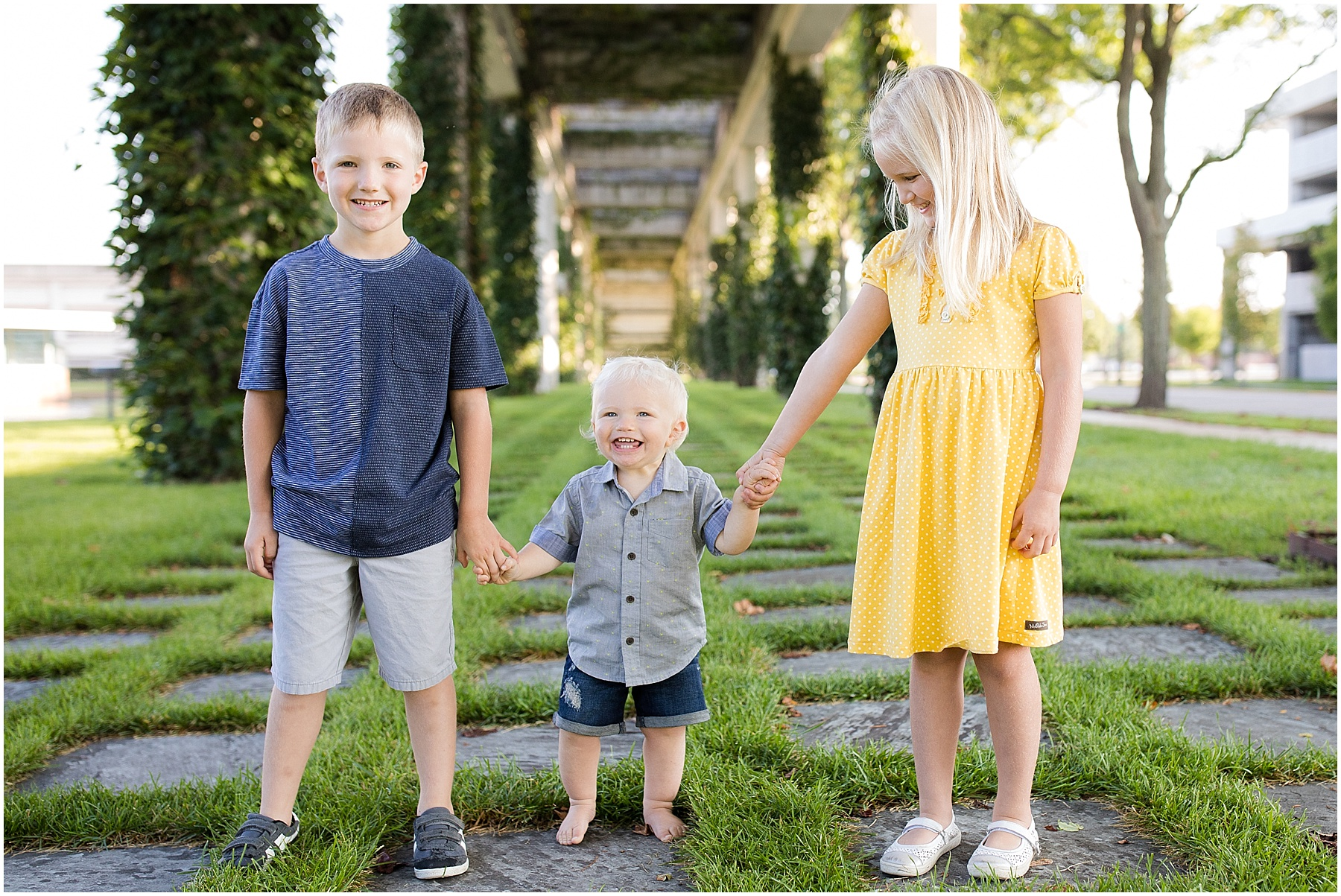 Brother and sister holding their one year old brothers hand, Columbus Family Photographer, Raindancer Studios