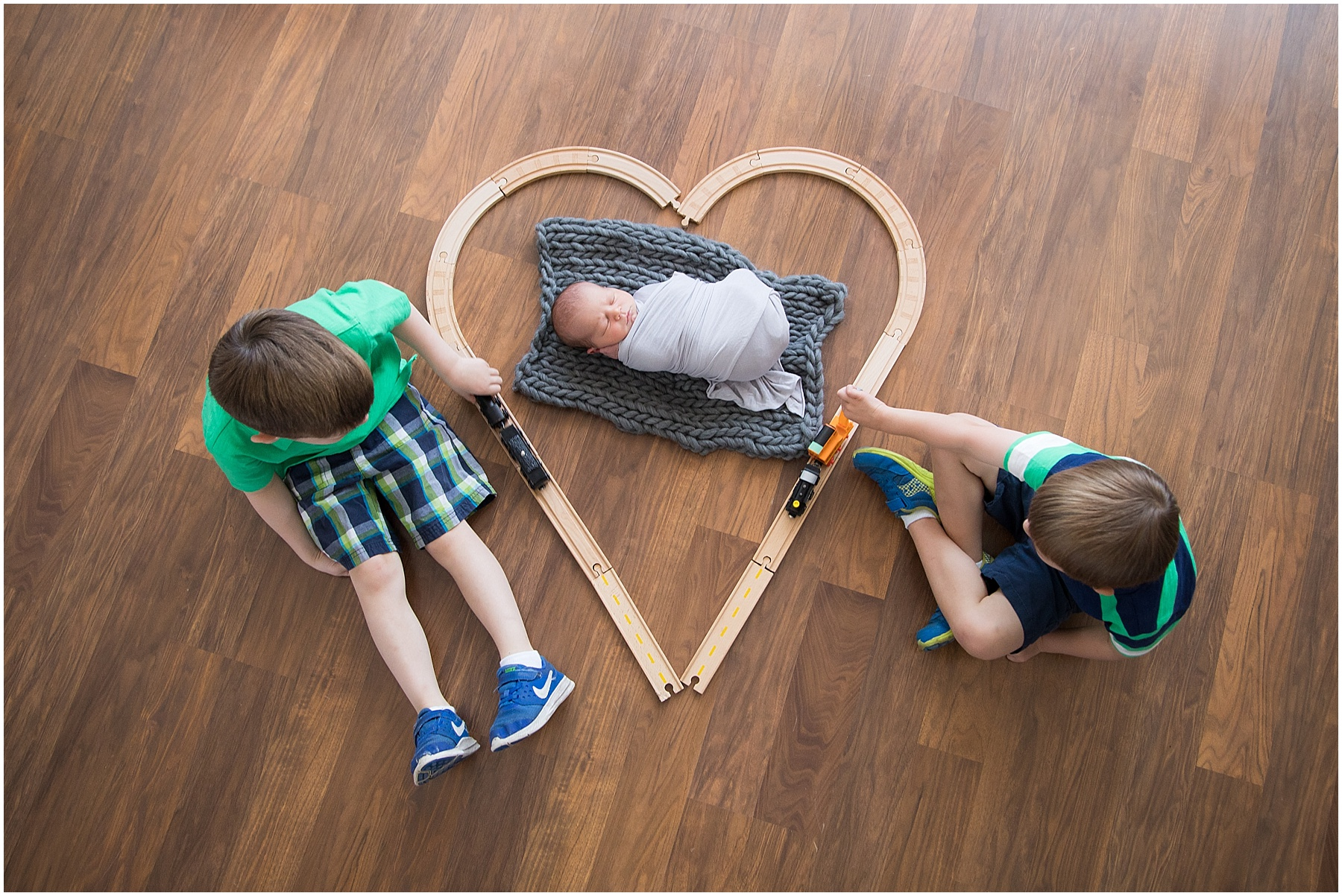 Brothers playing choo choo with their newborn baby brother, Indianapolis Child Photography, Raindancer Studios