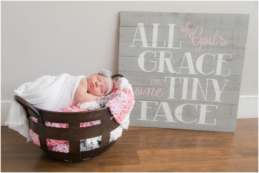 Baby girl in basket with sign. Taken by Raindancer Studios Newborn Photographer