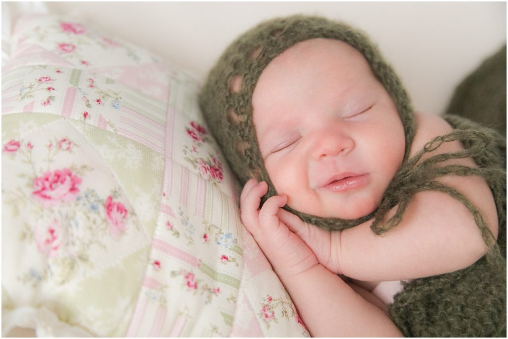 Smiling newborn girl with head on pillow. Indianapolis Baby Photography