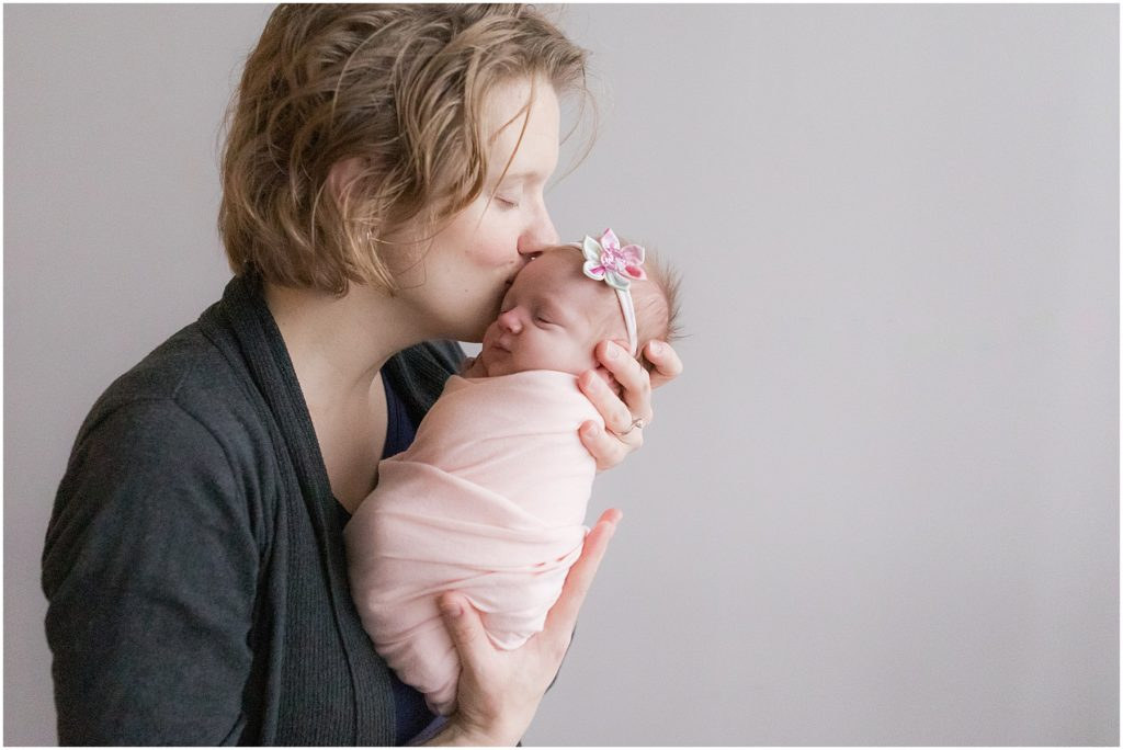 Mother kissing newborn girl on the forehead. Indianapolis Newborn Photography